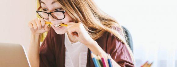 Palavras homófonas e homógrafas: imagem de uma menina mordendo o lápis e olhando para o notebook.