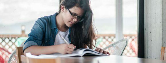 Imagem de uma menina olhando para um livro aberto na mesa e segurando um lápis.