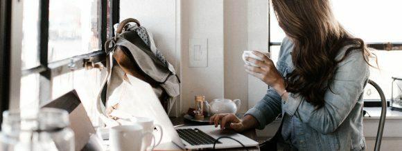 Diferença entre frase e oração: imagem de uma menina mexendo no notebook e com uma xícara de café na mão.