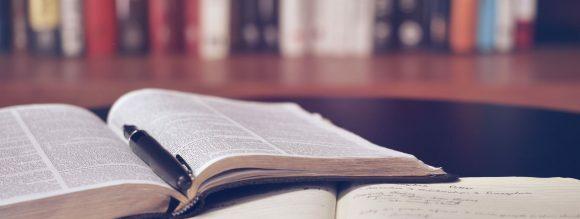 Transitividade verbal - imagem de dois livros abertos em uma mesa.