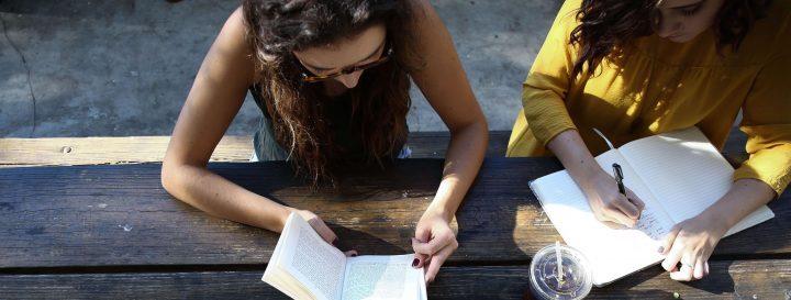 Imagem de duas meninas, uma lendo um livro e, a outra, escrevendo em um caderno.