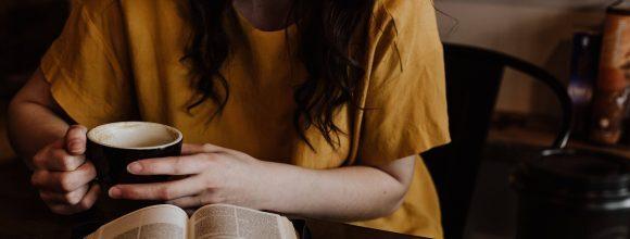 Imagem de uma menina lendo um livro que está em cima de uma mesa.