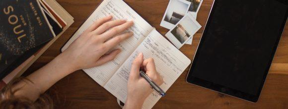 Advérbios - imagem de uma mesa com um caderno aberto e alguém escrevendo.