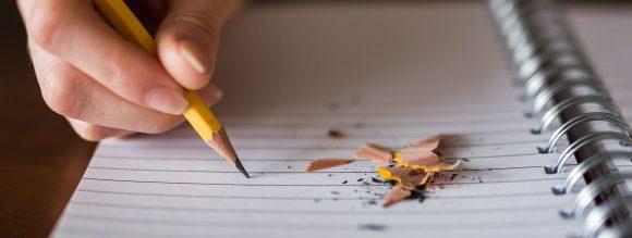 Coesão e coerência: imagem de um caderno aberto em uma mesa com um lápis por cima.