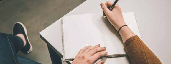 Uso de preposições: imagem de uma mão com caneta, apoiada em uma folha de papel em cima de uma mesa.