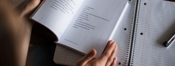 Regras de concordância nominal - imagem de um livro aberto com alguém lendo.