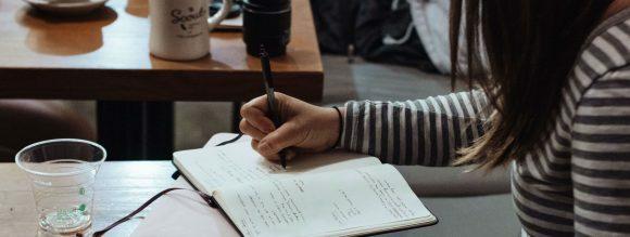 Imagem de um café com uma menina estudando em uma das mesas.
